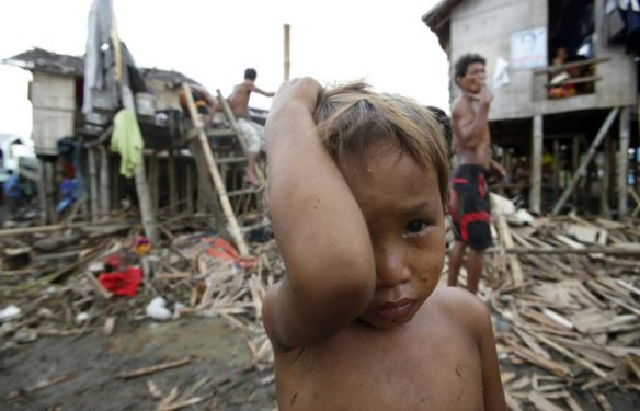 Typhoon victims stand outside their homes damaged by Typhoon Rammasun (locally named Glenda) in a village of sea gypsies, also known as Badjaos, in Batangas city, south of Manila, July 17, 2014. REUTERS/Erik De Castro