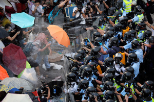 "Demonstrators' use of umbrellas to protect themselves from choking tear gas and stinging pepper spray has caused the demonstration to be dubbed the ""umbrella revolution."" Hong Kong authorities say that more than 40 people have been injured. (Photos: Vincent Yu/AP and Lam Yik Fei/Getty Images)"